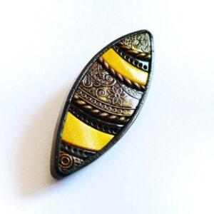 brož v žlutočerné barvě